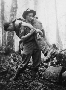 "Corporal Leslie ""Bull"" Allen carrying a soldier who had been knocked unconscious by a mortar round to safety during the assault on Mount Tambu in New Guinea on the 30 July 1943. Cpl Allen was awarded the American Silver Star for his action, rescuing 12 American soldiers during the battle. He had also received the Military Medal in February for his courage at Crystal Creek whilst serving with the 2/5th Infantry battalion."