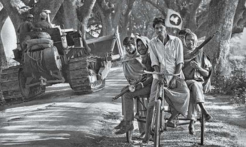 Mukti Bahini liberation fighters pull their rickshaw to the side of the road as an Indian Army Engineer unit passes by. Photographer unknown.