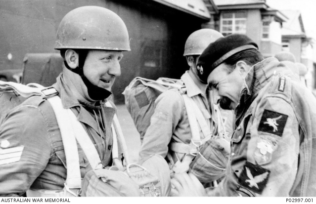 Douglas 'Dutchy' Holland wearing his distinctive 'patched-up' Dennison parachutist smock checking the parachute of trainee parachutist Sergeant John Cousins in October 1958. Photograph courtesy of the Australian War Memorial. Accession number P02997.001.