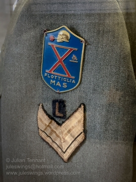 Shoulder badge detail from a jacket worn by medical personnel of the X-MAS (Decima Flottiglia MAS). On the top is the distinctive stamped metal formation badge. Sitting below is the rank badge of a sergeant yeoman and a bullion 'L' device indicating that the owner had university training.