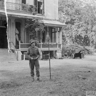 Major-General Robert E Urquhart, commanding 1st British Airborne Division, with the Pegasus airborne pennant in the grounds outside his headquarters at the Hartenstein Hotel in Oosterbeek, 22 September 1944. Photograph by Sergeant D.M. Smith (Army Film & Photographic Unit). Imperial War Museum accession number: BU 1136