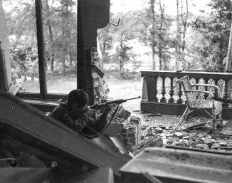 """A British Paratrooper taking aim with an American M1 carbine from the first floor balcony of the Hartenstein Hotel in Oosterbeek, near Arnhem in The Netherlands. September 1944. The photograph was taken by Sergeant D M Smith, Army Film & Photographic Unit on Saturday the 23rd of September 1944. Sergeant Dennis Smith, the photographer, wrote: """"We have had a very heavy shelling this morning, September 23rd and now the situation is serious. the shelling is hellish. We have been holding out for a week now. The men are tired, weary and food is becoming scarce, and to make matters worse, we are having heavy rain. If we are not relieved soon, then the men will just drop from sheer exhaustion"""". The British 1st Airborne Division headquarters had been established in the Hotel during 'Operation Market Garden' and it is now the Airborne Museum 'Hartenstein'."""