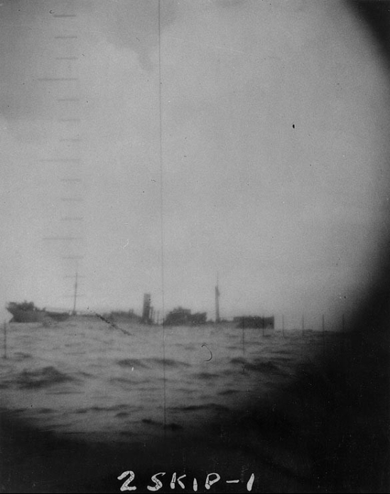 The Japanese Freighter S.S. Shunko Maru sinking in the central Pacific, after she was torpedoed by Skipjack (SS-184) on 14 October 1942. Photographed through Skipjack's periscope. Shunko Maru's back appears to be broken, and her hull bears traces of pattern camouflage paint. Photo: US National Archives # 80-G-33292