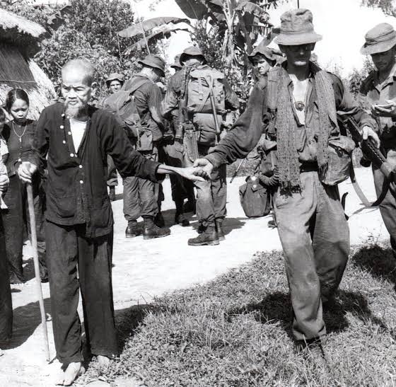 Corporal Lex McAulay, of 1st Battalion, The Royal Australian Regiment (1RAR), holds the hand of an old man as he leads him to safety after a village had been cleared of the Viet Cong. Photograph: Michael Shannon. Australian War Memorial Accession Number SHA/65/0220/VN