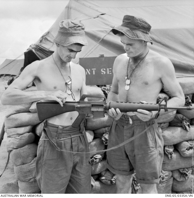 Bien Hoa, Vietnam. 1965-09. Two bare-chested Australians Corporal Lex McAulay (left) of Innisfail, Qld, and Corporal John Henderson of Macquarie Fields, NSW, inspect an Armalite rifle at the headquarters of the 1st Battalion, The Royal Australian Regiment (1RAR). Photograph: Bryan Dunne. Australian War Memorial Accession Number DNE/65/0335A/VN