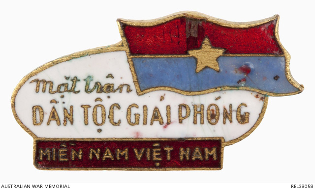 Viet Cong badge held in the Australian War Memorial collection of the same type to that affixed to Lex McAulay's lighter. The badge consists of a white enamel oval shape with 'MAI DAN TOC GIAI PHONG' written in raised brass lettering. In the top right of the badge is the Viet Cong flag, red over blue with a central yellow star in enamel. At the bottom of the badge is a red enamelled scroll with 'MIEN NAM VIET NAM' written in raised brass lettering. On the reverse of the badge is a pin and catch threaded into a small brass tube which has then been soldered onto the badge. This particular example was given to 213419 Lieutenant Alan George Hutchinson, a Royal Australian Artillery Forward Observer attached to the 1st Battalion, Royal Australian Regiment (1 RAR) during Operation Crimp in January 1965. Is it possible that this badge came from the same matchbox of badges given to Lex McCaulay during the operation? Australian War Memorial Accession Number REL38058