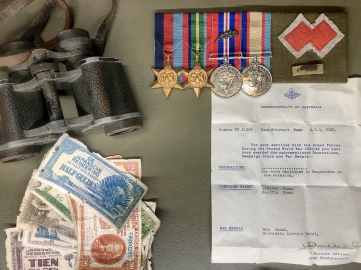 Medals, binoculars, Japanese Occupation currency and the distinctive red 'double diamond' commando unit colour patch belonging to Sgt Arthur Wray (MID) of the 2/2 Independent Company which waged a guerilla campaign against the Japanese in Timor from December 1941 until December 1942. Photo: Julian Tennant