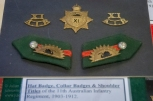 Hat badge, shoulder titles and collar badges of the 11th Australian Infantry Regiment, 1903 - 1912. Photo: Julian Tennant