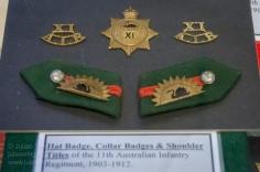 Hat badge, shoulder titles and collar badges of the 11th Australian Infantry Regiment, 1903 - 1912. Photo: Julian Tennant