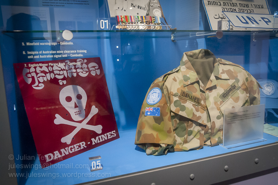Mine warning sign and shirt worn by Corporal Steve Danaher (RASIGS) whilst deployed to Cambodia as part of the UNTAC mission in 1993. Photo: Julian Tennant