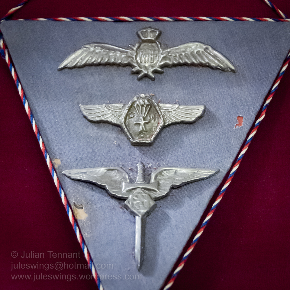 3 badges made from silver foil used in cigarette packets. These were made in 1944 by Sgt K.T. Sneider, a Czech POW. The cord represents the Czechoslovkian national colours. Top to bottom - RAF Pilot Wings, POW Parachute club and a Czech Air Force Badge. Photo: Julian Tennant