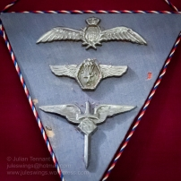 3 badges made by a Prisoner of War from silver foil used in cigarette packets. These were made in 1944 by Sgt K.T. Sneider, a Czech POW. The cord represents the Czechoslovkian national colours. Top to bottom - RAF Pilot Wings, POW Parachute club and a Czech Air Force Badge. Photo: Julian Tennant
