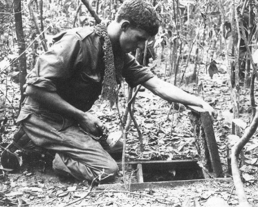 An Australian sapper from 3 Fd Tp looks into a Viet Cong tunnel in the Ho Bo Woods, north-west of Saigon, during Operation CRIMP. This operation marked the first time Allied (US and Australian) forces discovered and explored the VC's extensive tunnel network. Photographer: Unknown