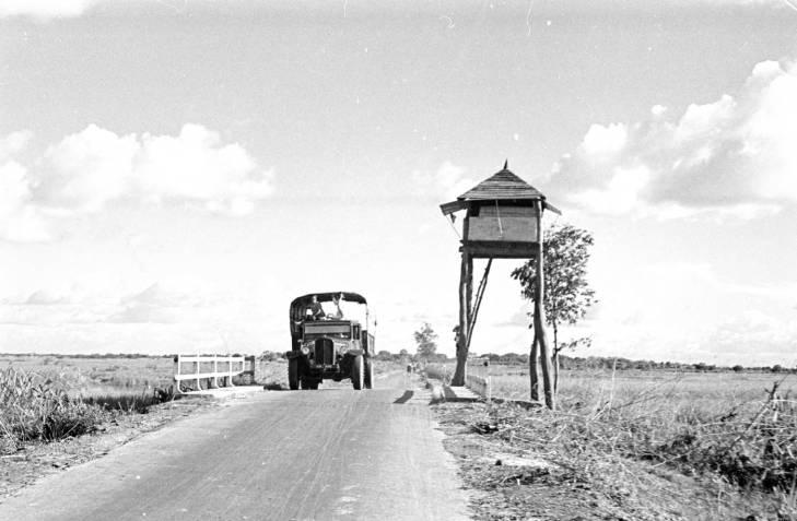 Vietnam, truck passing watchtower on stilts in Tây Ninh