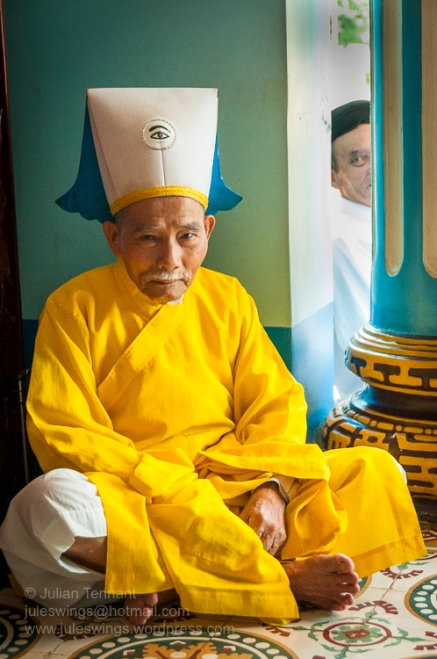 """Cao Đài bishop (denoted by the """"Divine Eye"""" embroidered onto his headpiece) waiting for the midday service at the Holy See in Tây Ninh. Photo: Julian Tennant"""