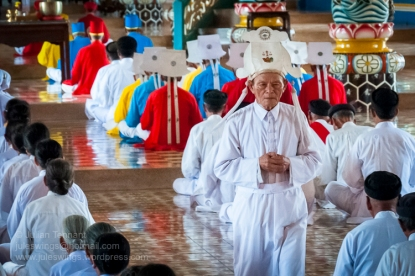 """Tay Ninh, 96km northwest of Ho Chi Minh City is home to the """"Holy See"""" of the once powerful Cao Dai religious sect. Founded in 1926 and based on messages revealed in séances to it's founder, Ngo Minh Chieu, Cao Dai incorporates elements of Buddhism, Hinduism, Taoism, Confucianism and Spiritualism. It's pantheon of deities includes Buddha, Confucius, Jesus Christ, Mohammed, Joan of Arc, Sun Yat Sen and Victor Hugo amongst others. The clergy is based on the Roman Catholic hierarchy and headed by a 'pope'. In the 1930's the sect became increasingly nationalistic and organised it's own militias, running Tay Ninh province as an almost independent feudal state. They were involved in revolts against the French before and during WW2, co-operating with the Japanese and then allying themselves to the Viet Minh in the early years of the post war struggle against the French administration. A pragmatic group they switched sides, giving nominal allegiance to the Emperor Bao Dai and the French, whilst still retaining anti-French sentiment. The Cao Daists provided the basis for the 'Third Force' in Graham Greene's classic novel, """"The Quiet American"""" and by 1956 boasted an army of about 20 000 troops. During the second Indochina war (known to the Vietnamese as the 'American war') they were allied to the South Vietnamese government and refused to aid the Viet Cong, a point not lost to the Communists who redistributed their lands and executed a four of their leaders after taking power. It wasn't until 1985 and the Cao Dai had been thoroughly pacified were they allowed to once again take control of their 'Holy See' and some 400 temples across Vietnam. Today it is estimated that there are some 2 – 3 million followers world wide. All Cao Dai temples hold religious ceremonies every six hours starting at midnight during which the clergy and lay people perform an elaborate, regimented ritual which includes offerings of incense, tea, alcohol, frui"""