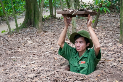 Guide demonstrating a tunnel entrance at the Cu Chi Tunnels tourist park. Photo: Julian Tennant