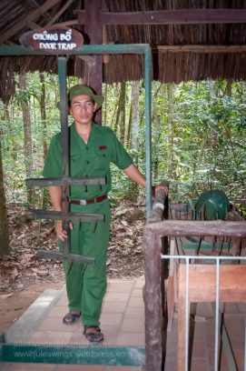 Tour guide demonstrating one of the booby traps at the Cu Chi Tunnels park. Photo: Julian Tennant