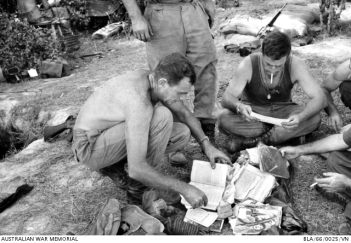 Truckloads of Viet Cong documents were captured by troops of 1st Battalion, Royal Australian Regiment (1RAR), when they unearthed a huge tunnel complex in the area known as Ho Bo Woods, north-west of Saigon, in Operation Crimp. Warrant Officer Second Class Jack Cramp (left) of Chester Hill, Sydney, NSW, and Major John Healy of Camberwell, Melbourne, Vic, sort some of the documents before despatching them to headquarters. Photo: Kenneth Ray Blanch. Australian War Memorial Collection Accession Number: BLA/66/0025/VN