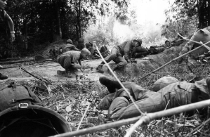 American soldiers of the US 28th Infantry's 1st Battalion scramble for cover as Viet Cong guerrillas open fire from concealed tunnels in an enemy stronghold 25 miles northwest of Saigon, Jan. 9, 1966. The unit, part of Operation Crimp, a massive allied assault, had just settled down for lunch when the Viet Cong attacked. (AP Photo/Horst Faas)