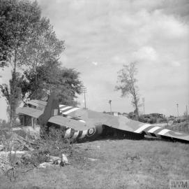 A Horsa glider near the Caen Canal bridge at Benouville, 8 June 1944. This is glider No. 91, which carried Major John Howard and Lieutenant Den Brotheridge with No.1 Platoon, 'D' Company, 2nd Battalion Oxfordshire and Buckinghamshire Light Infantry. It was one of the six gliders that carried 6th Airborne Division's 'coup de main' force - commanded by Major Howard - which captured the bridges over the Orne and Caen Canal in the early hours of D-Day. Photograph: Sergeant Christie. No. 5 Army Film and Photo Section, Army Film and Photographic Unit Imperial War Museum Catalogue Number: B 5232