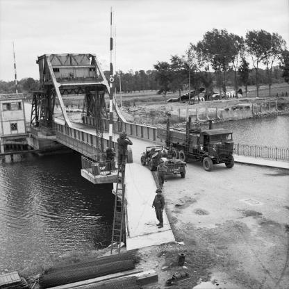 Pegasus Bridge, 9 June 1944. Vehicles including a Royal Signals jeep & trailer and a RASC Leyland lorry on 'Pegasus Bridge' over the Caen Canal at Benouville. The signallers are fixing telephone lines across the bridge. Photograph: Sergeant Christie. No. 5 Army Film and Photo Section, Army Film and Photographic Unit Imperial War Museum Catalogue Number: B 5288