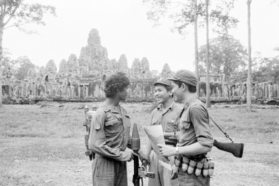 A Cambodian (L) and two Vietnamese soldiers converse outside the Angkor Wat temple in Angkor, Siam Reap, Cambodia, in 1982. Photo by Vietnam News Agency