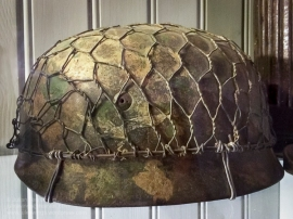 German Luftwaffe para helmet with wire camouflage net on display at Dead Man's Corner Museum, Normandy, France. Photo: Julian Tennant
