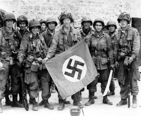 American paratrooper James Flanagan (2nd Platoon, C Co, 1-502nd PIR), among the first to make successful landings on the continent, holds a Nazi flag captured in a village assault. Marmion Farm at Ravenoville, Utah Beach, France. 6 June 1944. Source: US-Army history images