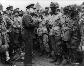 General Dwight D. Eisenhower addresses American paratroopers from E Co. 502nd PIR, on the afternoon before D-Day. The paratrooper with the number 23 around his neck is Lt Wallace C. Strobel who was the jumpmaster for that aircraft number in the packet. U.S. Army photograph. No. SC 194399