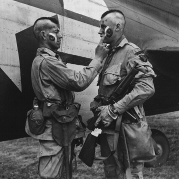 """Paratroopers Clarence C. Ware and Charles R. Plaudo from HQ Co. 506 PIR. 101 Abn Div, painting each other's faces on the afternoon of June 5, 1944. This phot was printed in Stars and Stripes, and helped form the legend of """"The Filthy Thirteen. US National Archives Accession Number: 111-SC-193551"""