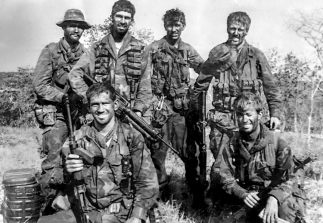 Nui Dat. SAS Hill, South Vietnam. 1971-04-08. Members of patrol Two Five, 'F' Troop, 2 Squadron, Special Air Service (SAS) at Nadzab LZ after returning from their second patrol. The patrol of nine days was from 30 March until 8 May 1971. Left to right, back row: Corporal Ian Rasmussen (patrol 2IC), Trooper Don Barnby (patrol signaller), Trooper Dennis Bird (patrol scout), 2nd Lieutenant Brian Russell (patrol commander). Front row: Trooper Bill Nisbett (rifleman), John Deakin (USN-SEAL attached). AWM Accession Number: P00966.084