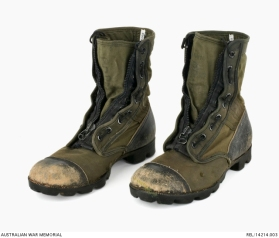 United States experimental tropical pattern boots : Trooper D R Barnby, 2 Squadron, Special Air Service Regiment. Description: Pair of experimental United States Army tropical boots. The black leather nose caps of both boots are heavily worn, exposing raw leather. The heel of each boot is also black leather. The body and tongue of each boot consists of olive green nylon. A large metal and black nylon zip secures the boots. A vertical lacing system is a feature of the boots, incorporating eighteen metal eyelets per boot and black nylon cord. There are a pair of circular brass eyelets on the inside arch of each boot, for removing excess water. The soles of both boots are black rubber which are worn from use. AWM Accession Number: REL/14214.003
