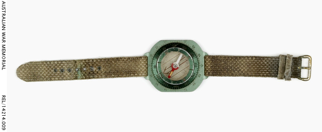 Wrist compass : Trooper D R Barnby, 2 Squadron, Special Air Service Regiment. Description: Wrist mounted magnetic compass, finished in medium green aluminium and fitted with a worn olive green nylon wrist strap. The compass has degrees etched into the edge of the rotating dial and mils indicators every 10 mils etched into the body. A small arrow is etched into the top of the compass body, next to the wrist strap. An index pointer consisting of a pair of 2 mm high vertical lines, separated by a small 1 mm diameter dot are stamped into the rotating dial. An orienting arrow and parallel orienting lines, marked in red, are fitted to the base of the compass on a rotating housing. The wrist strap has seven 2 mm diameter metal bounded holes centrally placed for adjusting the size. An indent with remnants of an unknown blue-green substance (possibly verdigris) is on the fourth hole. This indent corresponds with the wrist band metal buckle. The wrist band is fitted with a pair of horizontally arranged 5 mm diameter bands for securing the excess wrist band length. One of these horizontal bands is adjustable along the wrist band and the other, in a lesser condition, is stitched to the buckle arrangement. History / Summary Infantry and Special Forces troops on operations, need to carry a wide range of equipment such as navigational aids to successfully conduct their patrols. It is critical that these objects are as light and as compact as possible to save valuable space and weight. This commercially available self wrist compass is an example of this attitude; recent advice notes that these Silva compasses were purchased and supplied by the the American CISO (Counter Insurgency Support Office). AWM Accession Number: REL/14214.009