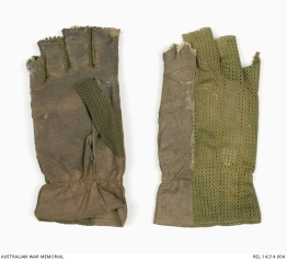 US tropical pattern gloves : Trooper D R Barnby, 2 Squadron, Special Air Service Regiment. Description Two right hand, olive green, US issued tropical gloves with the tops of all fingers removed. Two thirds of the top surface of the gloves is made from an olive green nylon mesh, with the index finger being entirely covered with Nomex. This Nomex extends up the entire length of the upper glove to the cuff. The palms of the gloves are made from a worn Nomex material. The stitching for one of the glove's right thumb is slightly frayed, and has come undone, with the other one entirely missing. The glove with the missing thumb also has a blue-green coloured number 9 hand written midway along the top of the glove above the index finger. This glove is also of a slightly lighter coloured olive green colour than the other. Around the cuff of the gloves is zig-zag stitching which slightly blouses the gloves. History / Summary These gloves were modified and worn on operations, to help protect the wearer's hands from the harsh conditions of the jungle and when using weapons. They also provided a form of camouflage for the exposed hands of the wearer, Trooper Don Barnby. AWM Accession Number: REL/14214.004
