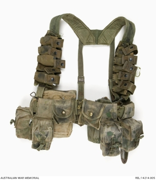 Composite webbing set : Trooper D R Barnby, 2 Squadron, Special Air Service Regiment. Description: A composite webbing set, consisting of standard US pattern waist belt, metal buckle and 'H' harness suspender. The suspender has been modified with the addition of five nylon webbing M79 40 mm grenade pouches, cut from a US Air Force survival vest, which are attached vertically down each front suspender strap. A blackened round brass press button secures each grenade pouch cover. Worn at the back of the belt is a large Australian 1937 Pattern basic canvas pouch and a British 1944 Pattern water bottle and carrier. In place of the standard Australian issue basic pouches at the front are twin US Special Forces M16 5.56 mm magazine pouches and two compass pouches, one containing insect repellent. Attached to the 1937 Pattern pouch is another compass pouch, containing another insect repellent container and inside the pouch is a field dressing. The webbing set has been hand camouflaged by adding random blotches of green and black paint. A US issue plastic M6 bayonet scabbard is also attached. AWM Accession Number: REL/14214.005