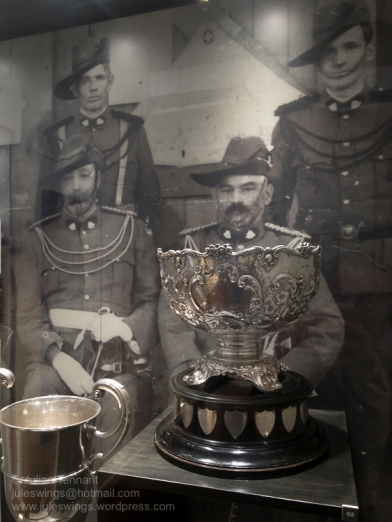 """Cabinet featuring to pre WW1 trophies. The trophy on the right, in the foreground, is the Matheson Challenge Cup (1901-1914) which was presented by Alec P. Matheson MLC to the Goldfields Volunteers Battalion in January 1901 and subsequently awarded during the annual sports day for team target shooting competitions. In the bottom left, just visible, is the Chamber of Mines of W.A. Challenge Cup 1902 - 1913 which was awarded annually to the 84th Senior Cadet Battalion company displaying the most prowess in """"field firing, inspection, company drill, skirmishing physical drill and march past"""". Photo: Julian Tennant"""