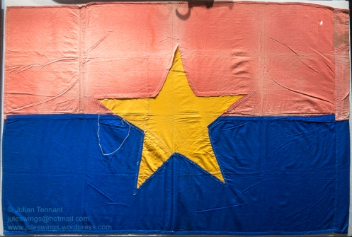 Viet Cong Flag captured by Private Ray Robinson of 11 Platoon, Delta Company, 4 Battalion RAR/NZ. . During Operation MERINO in July 1968 Ray's platoon uncovered a bunker system estimated to accomodate 15 people. After securing the bunker, Ray discovered a flag left behind by the retreating Viet Cong, a sewing needle mid-stitch still piercing the fabric. At the end of his tour of duty, Ray brought the flag home to the Goldfields where it lay forgotten in the bottom of a suitcase until it was found during a clean out and donated to the Goldfields War Museum. Photo: Julian Tennant