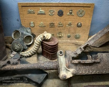 Badges, gasmask and 50 cal machine gun in one of the older displays at the Darwin Military Museum. Photo: Julian Tennant