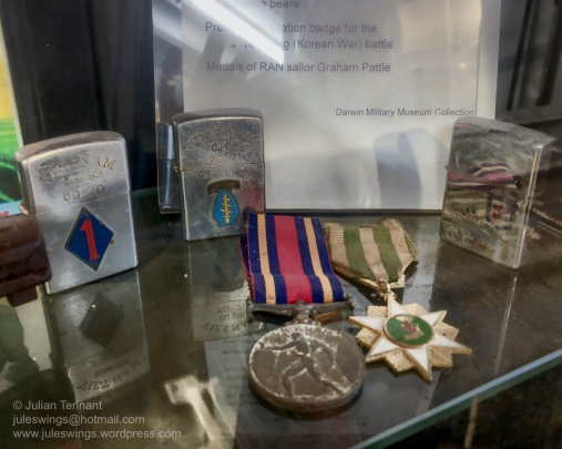 Vietnam War medals of Royal Australian Navy sailor Graham Pattle. The medal on the left appears to be the Vietnam Medal (reverse) but the ribbon is incorrect for the award. In the background are some Vietnam Zippo lighters. However I have reservations about the authenticity of these lighters ( which are one of my collecting areas) and unfortunately no details regarding their provenance is provided. Photo: Julian Tennant