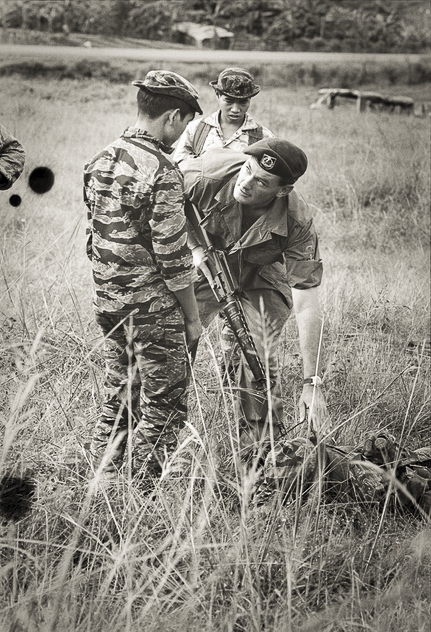 """This is how you do it."" Warrant Officer Class 2 (WO2) Lachlan Scowcroft of Holsworthy, NSW, shows one of his Montagnard soldiers how to search a captured enemy. Scowcroft joined Shilston's 211 Company on the second day of their attempt to break the siege of Dak Seang in April 1970. Photo: Christopher Bellis. Australian War Memorial Accession Number: BEL/69/0696/VN"