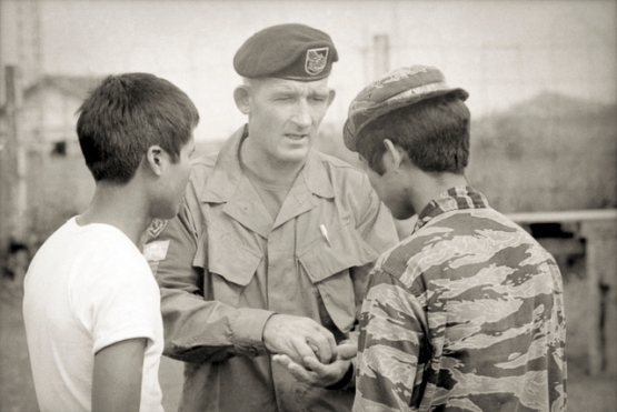 Pleiku, South Vietnam. 1969-10. Warrant Officer Class 2 (WO2) Alex McCloskey of Newcastle, NSW, explains a point to a Montagnard soldier of the II Corps Mobile Strike Force (Mike Force). McCloskey would be awarded the Distinguished Conduct Medal (DCM) for his actions during the action to break the siege of Dak Seang in April 1970. Photo: Christopher Bellis. Australian War Memorial Accession Number: BEL/69/0702/VN