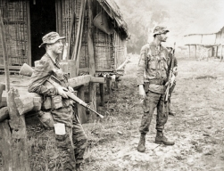 Pleiku, South Vietnam. July 1970. Australian Army Training Team Vietnam (AATTV) adviser, Captain (Capt) Peter Shilston of Williamtown, NSW (left), and an American adviser look on while Montagnard soldiers of the 1st Battalion, 2nd Mobile Strike Force search a village during an operation in central South Vietnam. Capt Shilston is commander of the Battalion which operates out of Pleiku. Photo: John Fairley. Australian War Memorial Accession Number: P00963.063