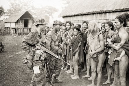 South Vietnam, July 1970. Australian Army Training Team Vietnam (AATTV) advisor, Captain Peter Shilston of Williamtown NSW, and Captain Ngac, South Vietnamese Army, question a Montagnard village chief about the population of the village in central South Vietnam. Soldiers of the 1st Battalion, 2nd Mobile Strike Force, placed a cordon around the village and carried out a search at first light. Captain Shilston is the commander of the battalion which operates out of Pleiku. Photo: John Fairley. Australian War Memorial Accession Number: FAI/70/0590/VN