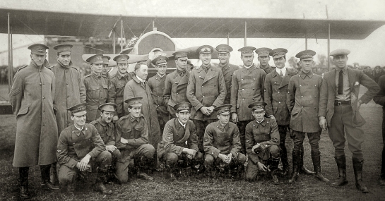 First student intake for the New South Wales State Aviation School, 28 August 1916. Back row, left to right: Nigel Love, who flew 200 hours over the front with 3 Sqn AFC; Garnsey Potts [briefly in 3AFC, invalided out due to sickness, thereafter instructing in England]; William L. King [joined 3AFC but crashed on a ferry flight with serious injuries, invalided to Australia]; Irving Sutherland [Royal Naval Air Service 10SQN, wounded in action]; Alan Weaver [joined 4AFC but soon seriously injured in a training accident]. Chief Instructor Billy Stutt (in centre, without cap); Augustus Woodward-Gregory [flew with 52SQN RAF, wounded in action, French Croix de Guerre]; John Weingarth [flew 151 missions over the lines in 4AFC Sopwith Camels, then instructing duties in England- died on a post-war training flight, 4 Feb 1919]; Jack Faviell [training and administration duties in England]; Edgar Coleman [joined RNAS, but dogged by illness and did not fly in combat]; Robert L. Clark [two months' combat with 2AFC, injured in an SE5A landing accident, thence instructing in England; died in WW2 as a civilian internee of the Japanese, when the Japanese POW ship Montevideo Maru was torpedoed by submarine USS Sturgeon on 1 July 1942]; Leslie Sampson [4AFC but suffered several accidents flying Camels and was grounded]; Roy Smallwood [combat with 4AFC for four months, shot down by German anti-aircraft fire, but survived]; Leonard Webber [left Richmond course but later saw action in Belgium]; and Charles Dagg [RNAS seaplane pilot, awarded Air Force Cross after he survived a wreck in the Mediterranean, died in WW2 serving in the RAF.] Front Row, left to right: Norman Clark [served with 3AFC for 9 months, pilot and Signals Officer, thence instructor in England, promoted to Captain and Flight Commander]; Cecil R. Burton [4AFC for two months, but invalided to England with illness]; Vernon Burgess [9SQN RFC and Flight Commander with 7SQN RFC on RE8s, shot down and wounded after six months in action, thence instruction duties]; Michael Cleary [served with 62SQN RFC, killed in action flying a Bristol Fighter, 28 March 1918 near Villers-Bretonneux, France]; Hector K. Tiddy [killed on a practice flight in France, 1917, 7SQN RFC]; and D. Reginald Williams [retained as an instructor at Richmond, then joined the AFC in England, but only employed ferrying new aircraft to France, due to medical restrictions.] Photo courtesy: The Nigel Love Photo Collection