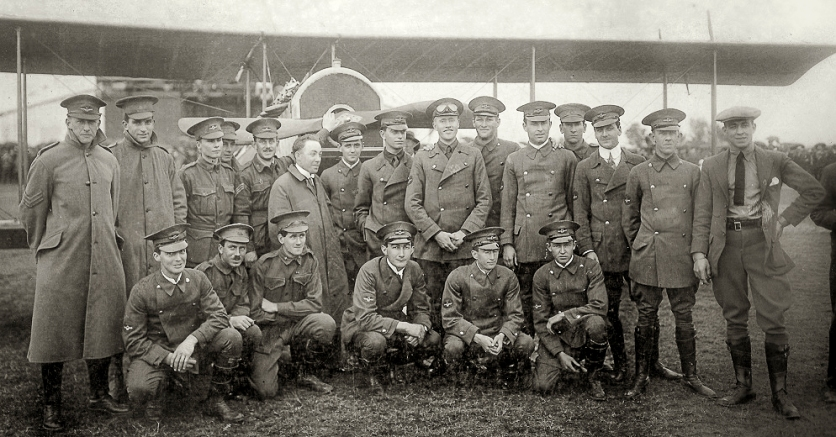 First student intake for the New South Wales State Aviation School, 28 August 1916. Back row, left to right: Nigel Love, who flew 200 hours over the front with 3 Sqn AFC; Garnsey Potts [briefly in 3AFC, invalided out due to sickness, thereafter instructing in England]; William L. King [joined 3AFC but crashed on a ferry flight with serious injuries, invalided to Australia]; Irving Sutherland [Royal Naval Air Service 10SQN, wounded in action]; Alan Weaver [joined 4AFC but soon seriously injured in a training accident]. Chief Instructor Billy Stutt (in centre, without cap); Augustus Woodward-Gregory [flew with 52SQN RAF, wounded in action, French Croix de Guerre]; John Weingarth [flew 151 missions over the lines in 4AFC Sopwith Camels, then instructing duties in England- died on a post-war training flight, 4 Feb 1919]; Jack Faviell [training and administration duties in England]; Edgar Coleman [joined RNAS, but dogged by illness and did not fly in combat]; Robert L. Clark [two months' combat with 2AFC, injured in an SE5A landing accident, thence instructing in England; died in WW2 as a civilian internee of the Japanese, when the Japanese POW ship Montevideo Maru was torpedoed by submarine USS Sturgeon on 1 July 1942]; Leslie Sampson [4AFC but suffered several accidents flying Camels and was grounded]; Roy Smallwood [combat with 4AFC for four months, shot down by German anti-aircraft fire, but survived]; Leonard Webber [left Richmond course but later saw action in Belgium]; and Charles Dagg [RNAS seaplane pilot, awarded Air Force Cross after he survived a wreck in the Mediterranean, died in WW2 serving in the RAF.] Front Row, left to right: Norman Clark [served with 3AFC for 9 months, pilot and Signals Officer, thence instructor in England, promoted to Captain and Flight Commander]; Cecil R. Burton [4AFC for two months, but invalided to England with illness]; Vernon Burgess [9SQN RFC and Flight Commander with 7SQN RFC on RE8s, shot down and wounded after six months in 