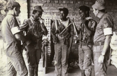 Two members of the Australian contingent from the Commonwealth Monitoring Force with ZANLA fighters at an assembly point.