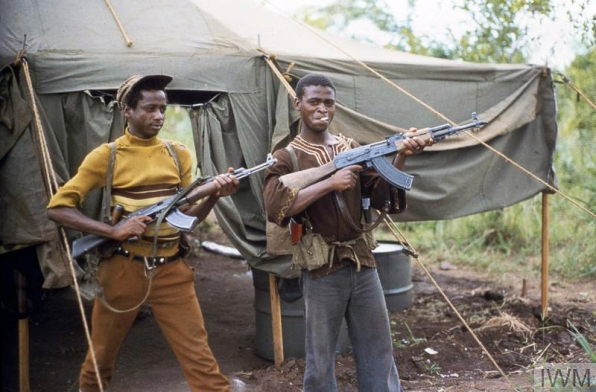 Op AGILA: Two guerillas display their Kalashnikov AK 47 weapons at Assembly Area Foxtrot, near the Rhodesian border with Mozambique, during the seven day ceasefire at the start of the peace process. During the ceasefire, 22,000 communist guerrilla fighters of Robert Mugabe's Zimbabwe National Liberation Army (ZANLA) and Joshua Nkomo's Zimbabwe People's Revolutionary Army (ZIPRA) gathered at sixteen assembly points in the lead up to the elections. Copyright: © IWM. Original Source: http://www.iwm.org.uk/collections/item/object/205191111